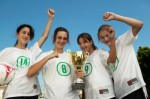 female-footballers-holding-trophy-arms-raised-celebration