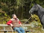 Reiter auf der Bank, Pferd daneben.