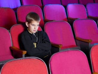 Boy waiting in movie theater